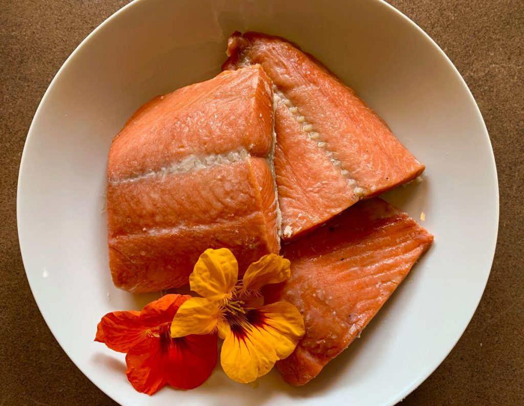 smoked salmon and an orange flower in a bowl