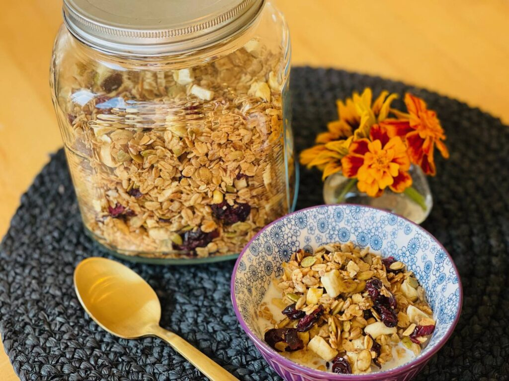 granola in a bowl with milk next to a jar of granola